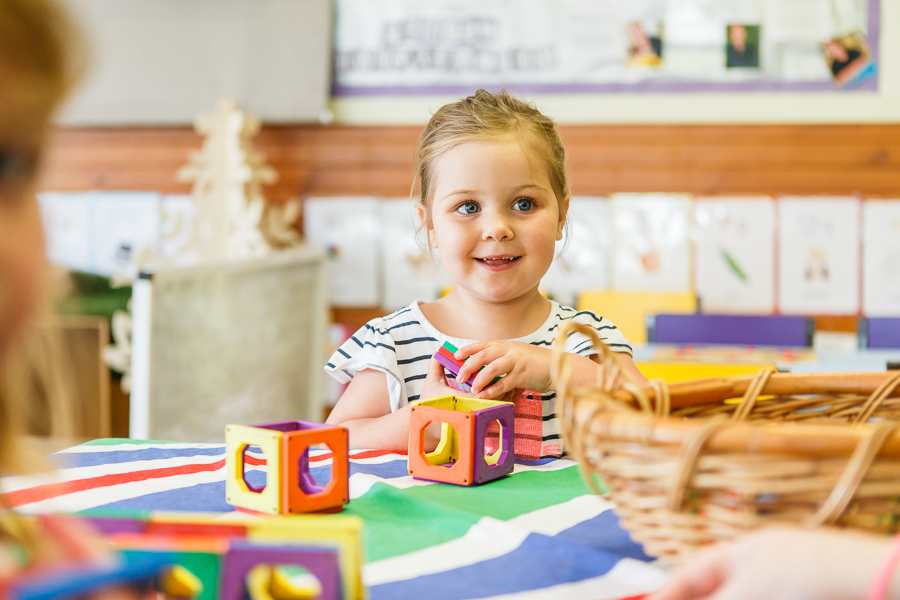 Young child playing with building blocks in child care classroom at Casey childcare and kindergarten