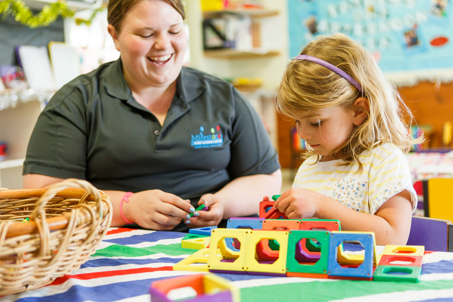 Child care educator helping child with building blocks at Casey Childcare and Kindergarten